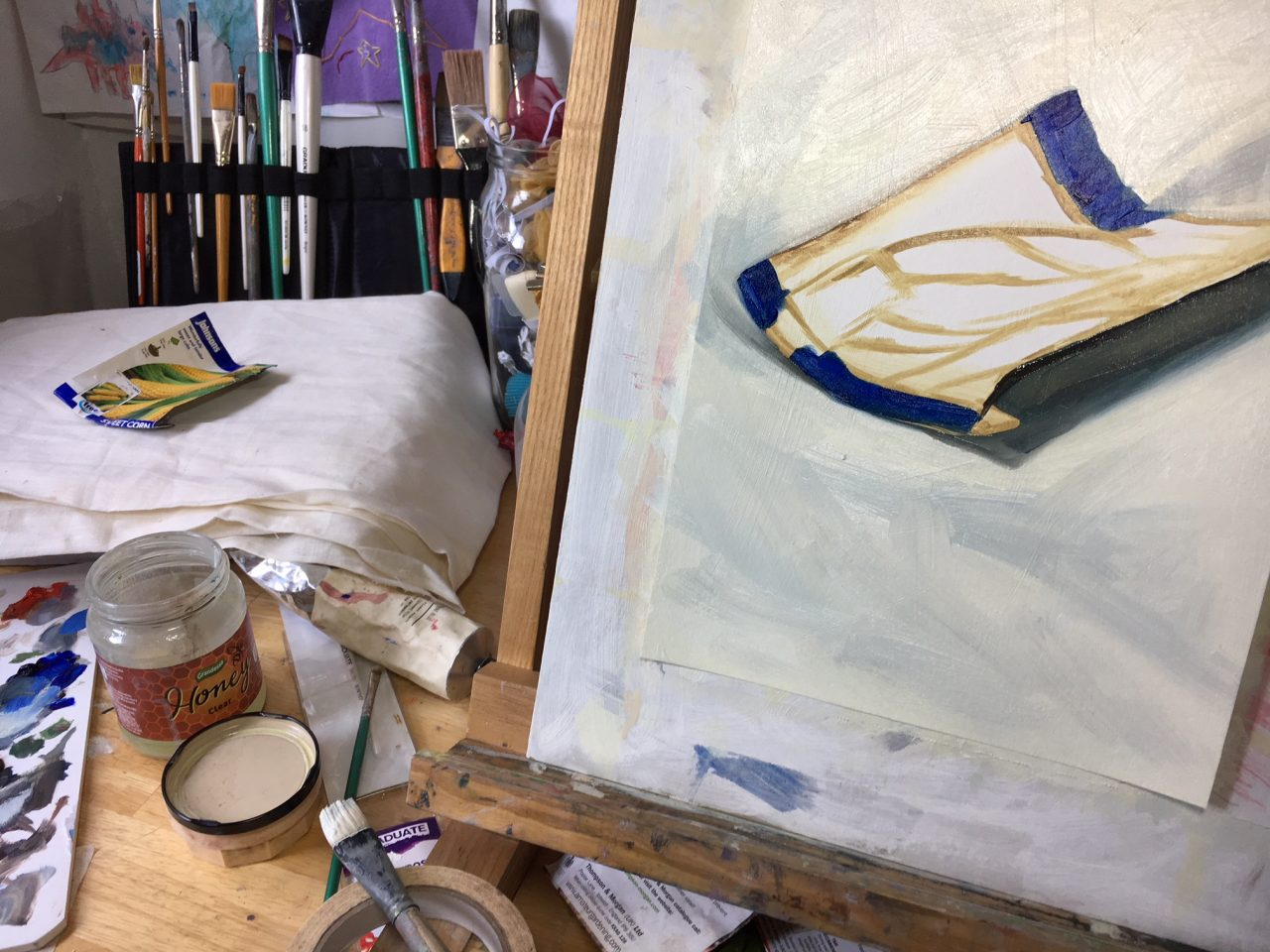Photo of work in progress - a painting on easel, alongside still life set up of seed packet